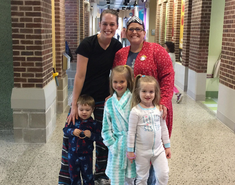 Two female adults and three children all wearing jammies smiling for the camera on Kidoodle Way at the Children's Museum