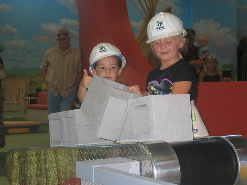 Girl and boy with hard hats on playing with pretend concrete blocks. Boy gives thumbs up