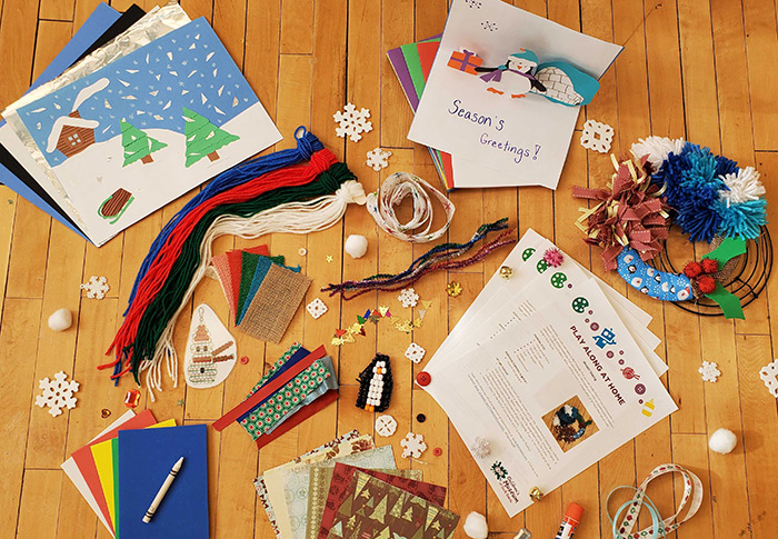 Craft materials such as paper, yarn, colorful paper and more displayed on a wooden floor.