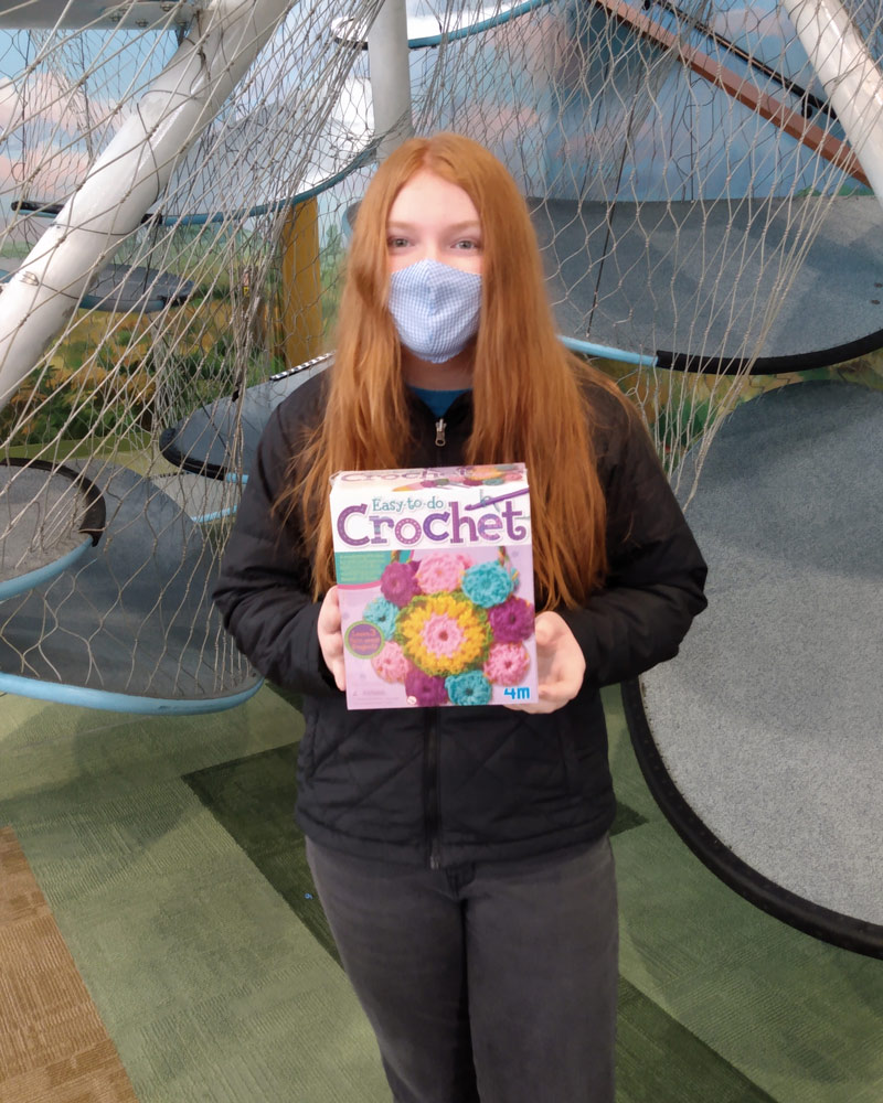 Girl in face covering holding up crochet kit.