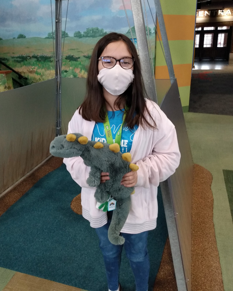 Girl in face covering holding up dinosaur plush.