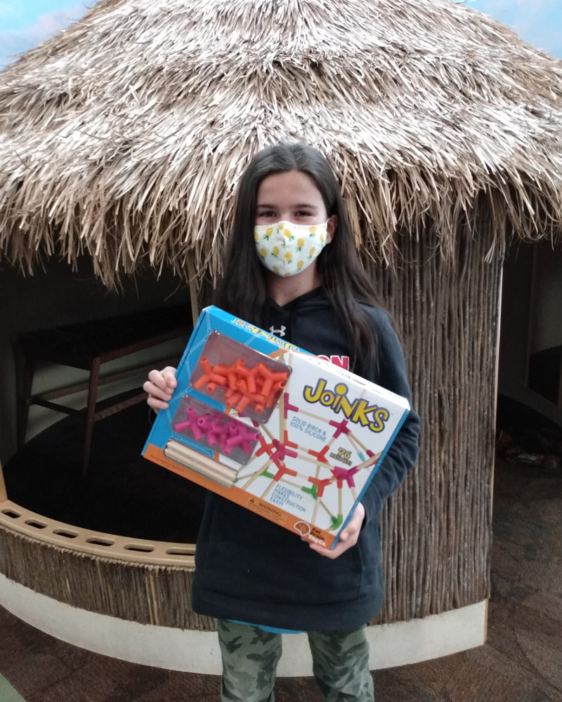 Girl in face covering holding up Joinks toy.