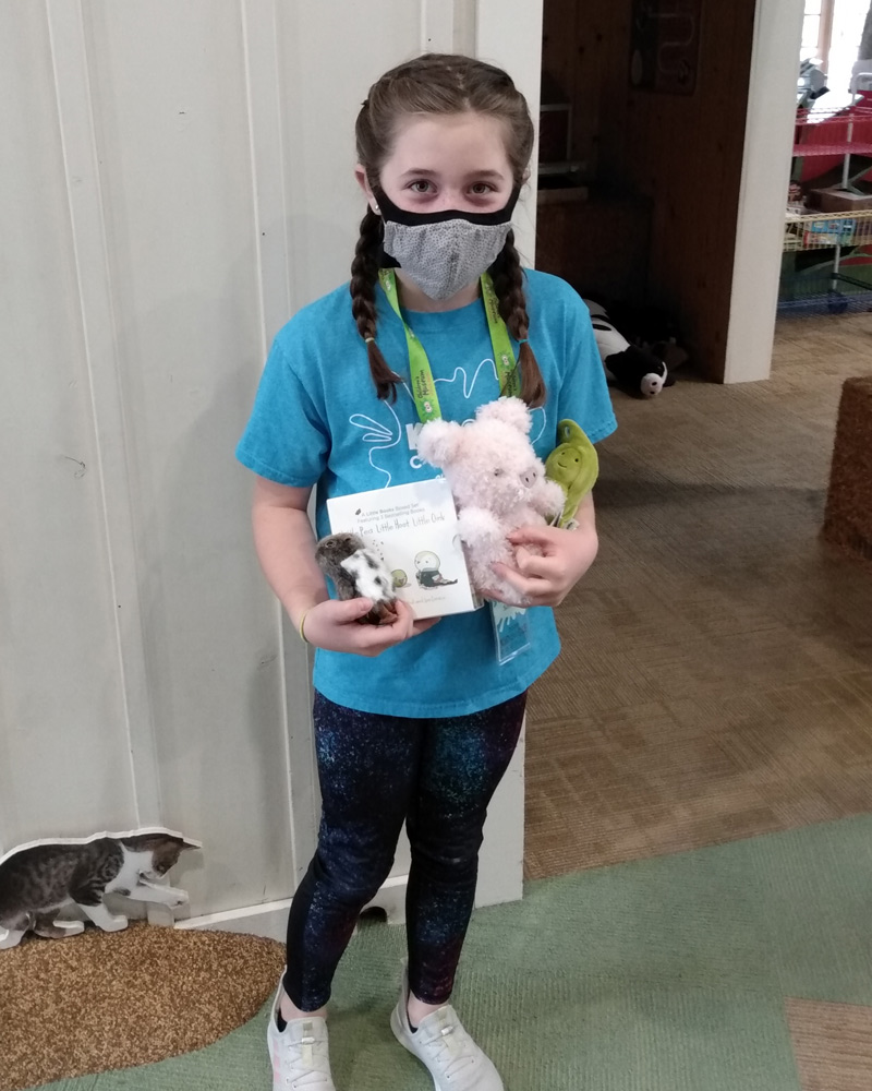 Girl in face covering holding up owl, pig, pea plush with a book set.