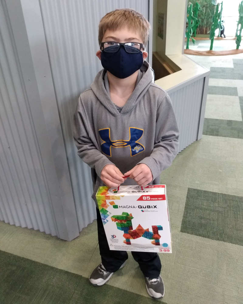 Boy in face covering holding up Magna Qubix toy.