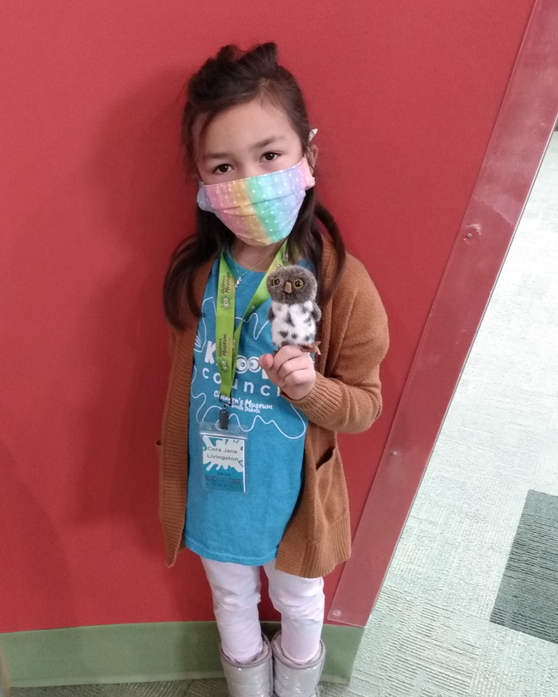 Girl in face covering holding up an owl finger puppet.