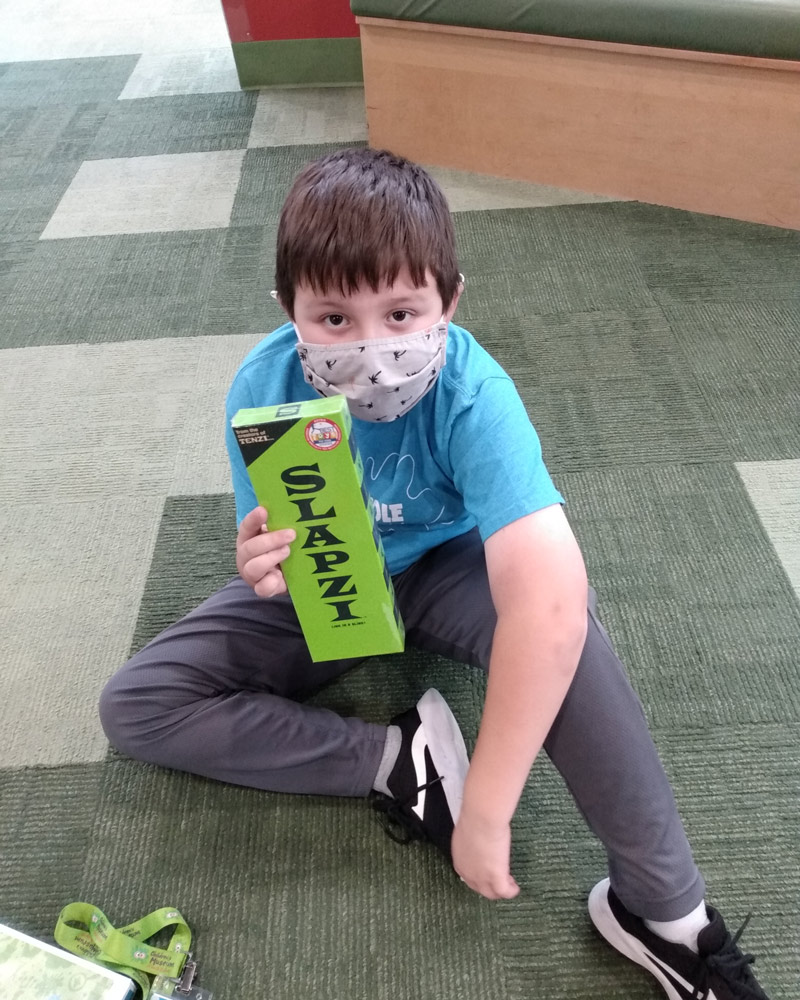 Boy wearing a face covering holding up Slapzi game.