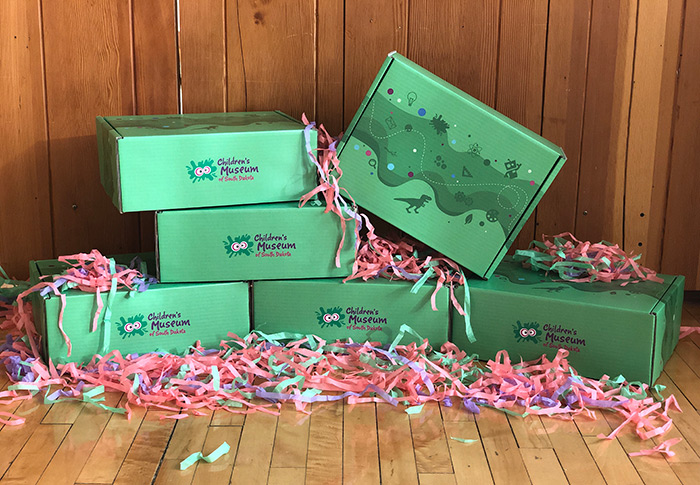 Green decorated boxes set up on wood floor with pink packaging materials nearby.