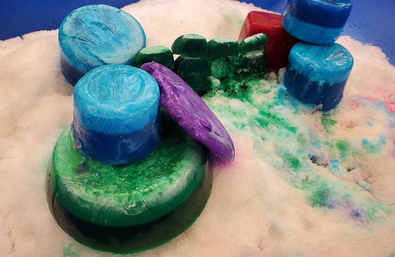 Blue, green, and purple ice chunks arranged in a sculpture.