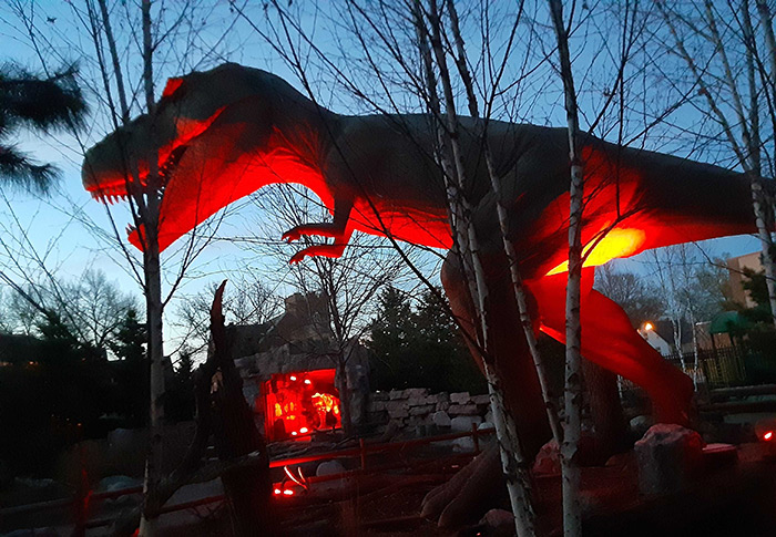 Mama T. Rex and Max are bathed in red light at dusk on the prairie of the Children's Museum of South Dakota.