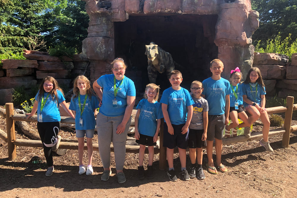 Kidoodle Council youth advisory board standing outside next to Max, an animatronic t. rex.