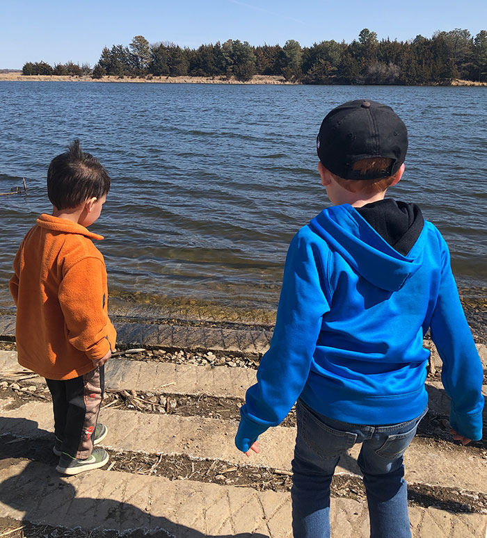 Two toddlers dressed in jackets and pants on a sunny day looking out onto a blue lake.